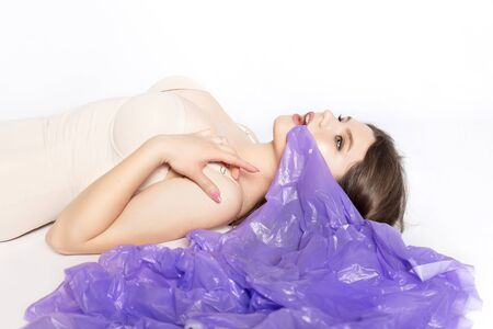 Young beautiful woman with a plastic bag in her mouth in the studio. The concept of ecology and environmental damage from plastic. High quality photo