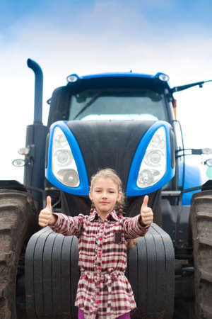 Cute girl near the modern tractor in the field. The concept of field work, agricultural machinery. Banco de Imagens - 155302623