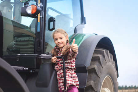 Cute girl near the modern tractor in the field. The concept of field work, agricultural machinery. Banco de Imagens - 155302642