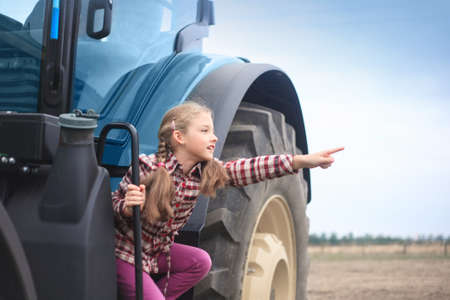 Cute girl near the modern tractor in the field. The concept of field work, agricultural machinery. Banco de Imagens - 155302656