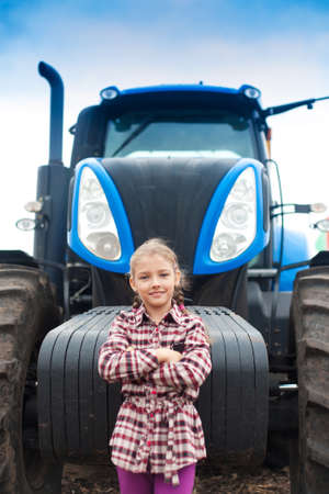 Cute girl near the modern tractor in the field. The concept of field work, agricultural machinery. Banco de Imagens - 155302658