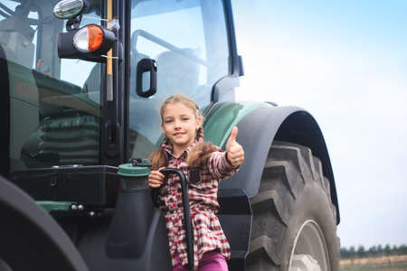 Cute girl near the modern tractor in the field. The concept of field work, agricultural machinery. Banco de Imagens - 155302661