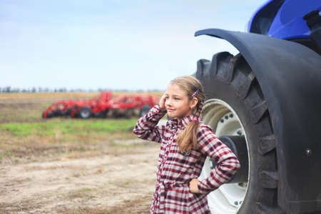 Cute girl near the modern tractor in the field. The concept of field work, agricultural machinery. Banco de Imagens - 155302669