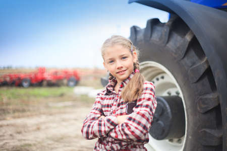 Cute girl near the modern tractor in the field. The concept of field work, agricultural machinery. Banco de Imagens