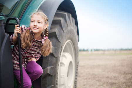 Cute girl near the modern tractor in the field. The concept of field work, agricultural machinery. Banco de Imagens - 155302672