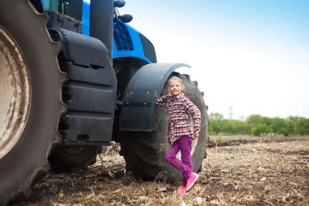 Cute girl near the modern tractor in the field. The concept of field work, agricultural machinery. Banco de Imagens - 155302681