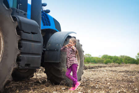 Cute girl near the modern tractor in the field. The concept of field work, agricultural machinery.