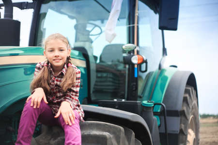 Cute girl near the modern tractor in the field. The concept of field work, agricultural machinery. Banco de Imagens - 155302687