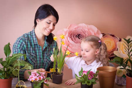 Cute child girl helps her mother to care for plants. Happy family on a studio. Banco de Imagens - 155302693