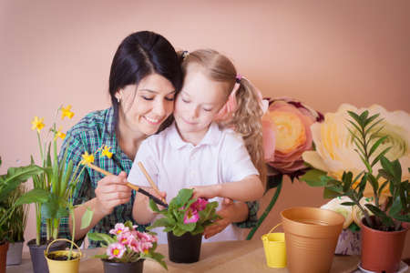Cute child girl helps her mother to care for plants. Happy family on a studio. Banco de Imagens - 155302695