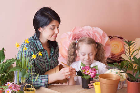 Cute child girl helps her mother to care for plants. Happy family on a studio. Banco de Imagens - 155302702