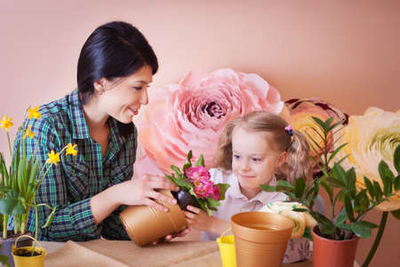 Cute child girl helps her mother to care for plants. Happy family on a studio. Banco de Imagens - 155302705