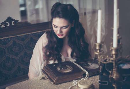 Young woman looks at a photo album. Vintage old style, retro interior. Banco de Imagens - 155302727