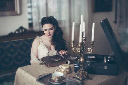 Young woman looks at a photo album. Vintage old style, retro interior. Banco de Imagens - 155302731