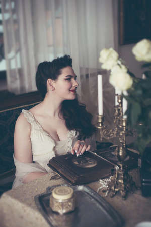 Young woman looks at a photo album. Vintage style, retro interior.