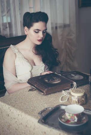 Young woman looks at a photo album. Vintage style, retro interior. Banco de Imagens - 153610899