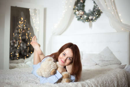 Young beautiful woman in pajamas in the bedroom. Winter holiday.