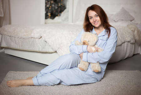 Young beautiful woman in pajamas in the bedroom. Winter holiday. Banco de Imagens - 153683611