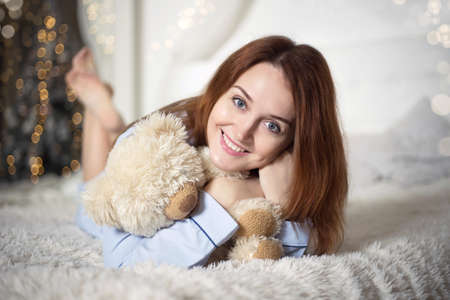 Young beautiful woman in pajamas in the bedroom. Winter holiday. Banco de Imagens - 153683615