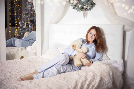 Young beautiful woman in pajamas in the bedroom. Winter holiday. Banco de Imagens - 153683621