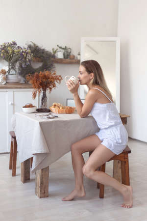 Young beautiful woman having breakfast in the morning in the kitchen. Banco de Imagens - 153763616