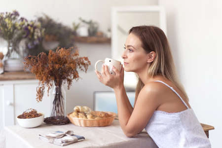 Young beautiful woman having breakfast in the morning in the kitchen.