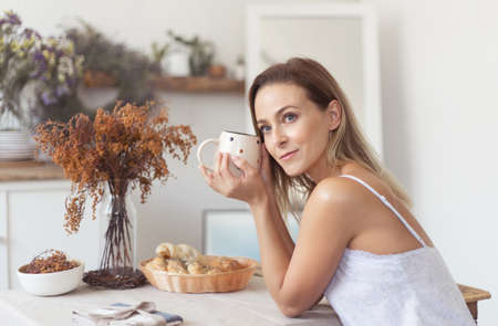 Young beautiful woman having breakfast in the morning in the kitchen. Banco de Imagens - 153763619