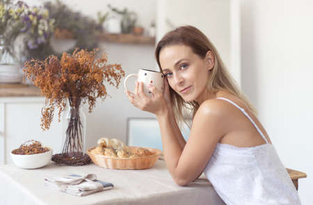 Young beautiful woman having breakfast in the morning in the kitchen. Banco de Imagens - 153763617
