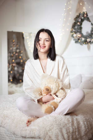 Young beautiful woman in pajamas in the bedroom. Winter holiday. Banco de Imagens - 153763618