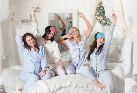Young pretty women in the bedroom, pajama party or bachelorette party. Time for New Year's holidays and Christmas holidays. Christmas, new year, holiday.