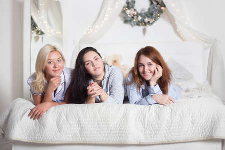 Young pretty women in the bedroom, pajama party or bachelorette party. Time for New Year's holidays and Christmas holidays. Christmas, new year, holiday. Banco de Imagens - 155302872
