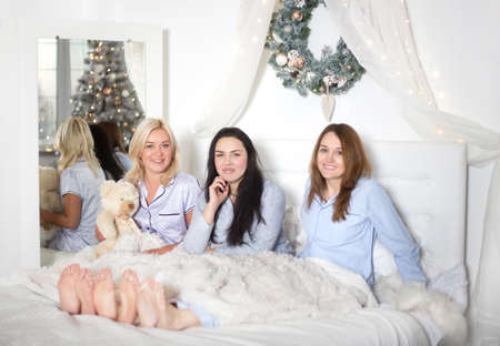 Young pretty women in the bedroom, pajama party or bachelorette party. Time for New Year's holidays and Christmas holidays. Christmas, new year, holiday. Banco de Imagens - 155302873