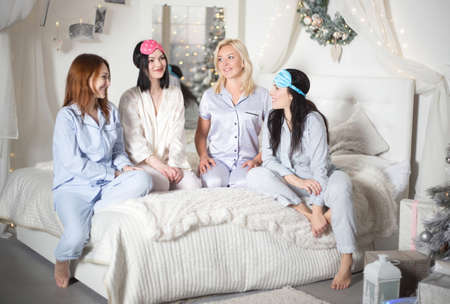 Young pretty women in the bedroom, pajama party or bachelorette party. Time for New Year's holidays and Christmas holidays. Christmas, new year, holiday. Banco de Imagens - 155302878