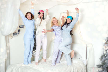 Young pretty women in the bedroom, pajama party or bachelorette party. Time for New Year's holidays and Christmas holidays. Christmas, new year, holiday. Banco de Imagens - 155302883