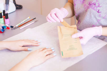 The manicurist opens an individual package with tools. Disinfection and sterilization. Safety. Close-up.