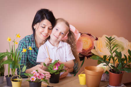 Cute child girl helps her mother to care for plants. Happy family on a studio. Banco de Imagens - 155236616