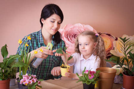Cute child girl helps her mother to care for plants. Happy family on a studio. Banco de Imagens - 155236688
