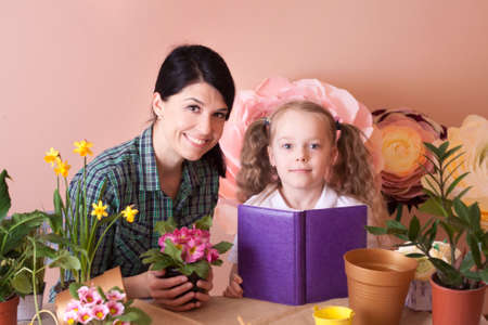 Mom and daughter take care of indoor flowers. Studio photo. Happy family on a studio. Banco de Imagens - 155302895