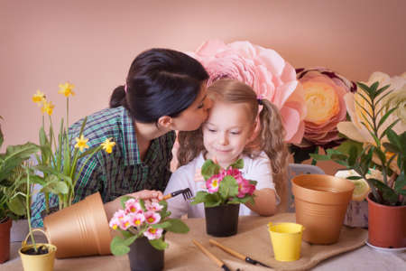 Mom and daughter take care of indoor flowers. Studio photo. Happy family on a studio. Banco de Imagens - 155236489