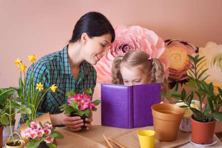 Mom and daughter take care of indoor flowers. Studio photo. Happy family on a studio.