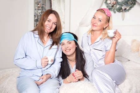 Beautiful young women are drinking tea in the bedroom. Studio photo. Christmas and New Year. Young pretty women in the bedroom, pajama party. Banco de Imagens - 155302912