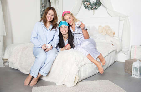Beautiful young women are drinking tea in the bedroom. Studio photo. Christmas and New Year. Young pretty women in the bedroom, pajama party. Banco de Imagens - 155302932