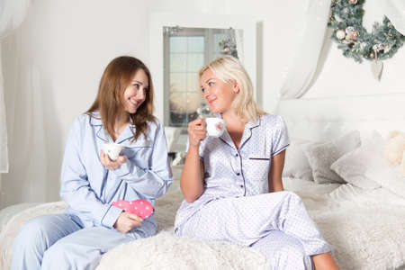 Beautiful young women are drinking tea in the bedroom. Studio photo. Christmas and New Year. Young pretty women in the bedroom, pajama party.