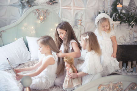 Little girls play in the bedroom in the morning before Christmas. The concept of family, sisterhood, friendship. Winter holidays, Christmas, New Year.