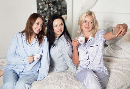 Beautiful young women are drinking tea in the bedroom and take selfies. Studio photo. Christmas and New Year. Young pretty women in the bedroom, pajama party.