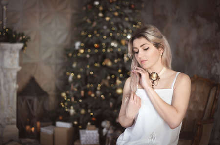 Beautiful young woman in the living room near the Christmas tree. Brooding or lonely, retro style. Studio photo. Banco de Imagens - 159368507