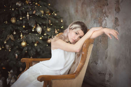 Beautiful young woman in the living room near the Christmas tree. Brooding or lonely, retro style. Studio photo. Banco de Imagens