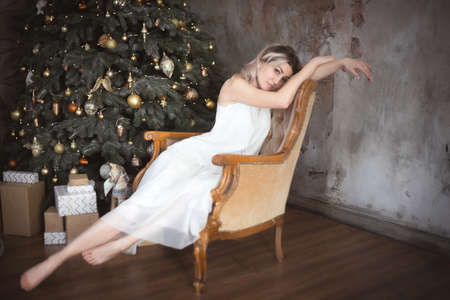 Beautiful young woman in the living room near the Christmas tree. Brooding or lonely, retro style. Studio photo. Banco de Imagens - 159371229