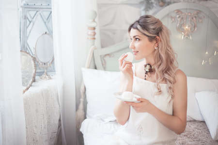 Cute young woman eating sweets in the morning in the bedroom. Gentle winter morning. Studio photo. Banco de Imagens