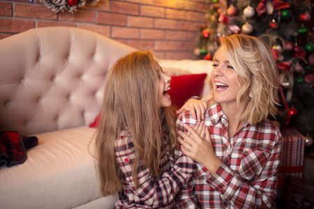 Happy mother and daughter near a Christmas tree fun laughing. Studio photo.